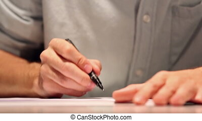 Man is drawing or writing on white sheet of paper. Macro...