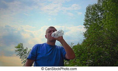 Man is drinking fresh water from a plastic bottle - Handsome...