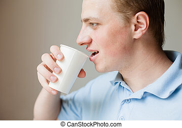 Man is drinking water from a paper cup