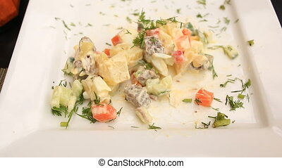 man is eating a potato salad with a square plate. close-up.