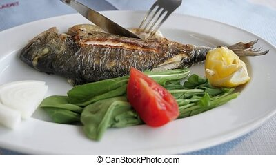 Man is eating frying fish with fork and knife in restaurant,...