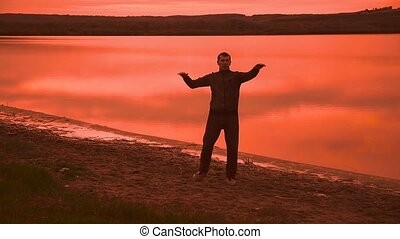 man is engaged in gymnastics yoga on the nature of the sunset silhouette red sport