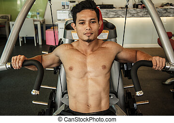 Man is exercising with machine bench press