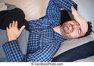Man is feeling headache and can't sleep