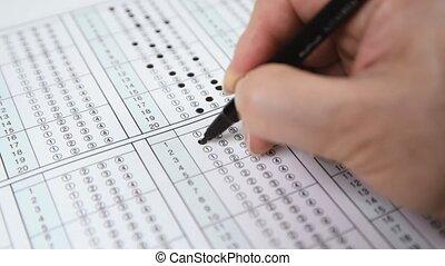 Man is filling OMR sheet handing with pen.