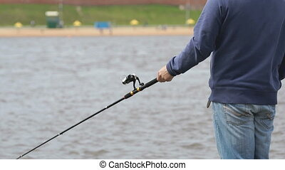 Man is fishing with a rod on background of river - Unknown...