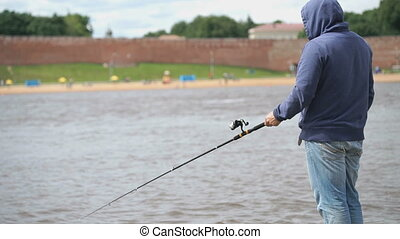 Man is fishing with a rod on background of river