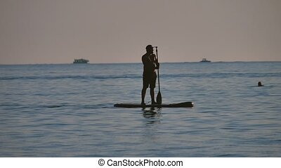 man is floating while standing in ocean paddle board. by the...
