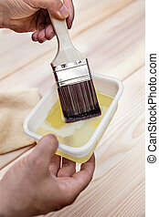 man is glazing a wooden table with a hair brush and oil