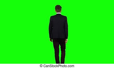 Man is going to a meeting and waving greetings. Green screen. Back view