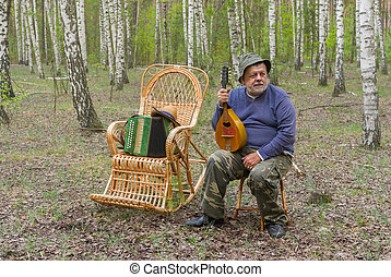 Man is having rest in birch forest, sitting on a wicker stool and holding mandolin