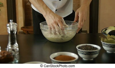 Man is kneading the bread dough in flour in the bowl glass