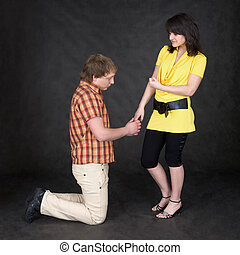 Man is kneeling to the young woman, being sorry - The man is...