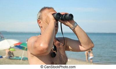 Man is looking through binoculars on beach