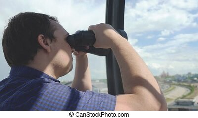 Man is looking through binoculars while rides on a ferris...