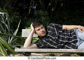 man is lying on a bench