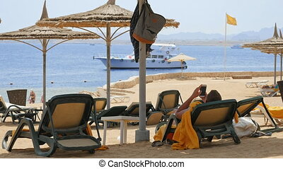 Man is lying on the beach couch under the umbrella - Man is...