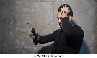 Man is making a hairdo using hairspray