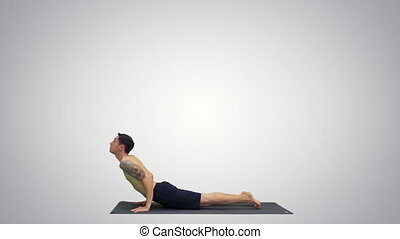 Man is making yoga poses on gradient background.