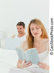 Man is on his laptop while his wife is reading a book
