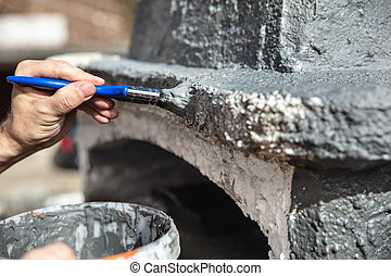 Man is painting an renewing a walled up barbecue with a paintbrush