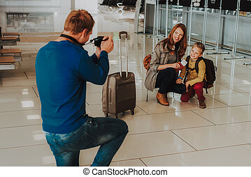 Man is photographing wife and son before departure