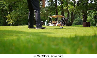Man is playing a drive with a golf caddie in the background