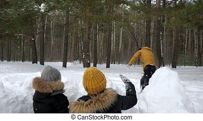 Man is playing snowballs with his family, wife and little son hiding before snow wall.