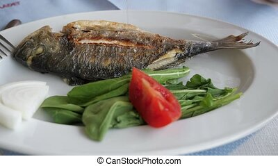 Man is pouring fish with lemon juice on the plate with green...