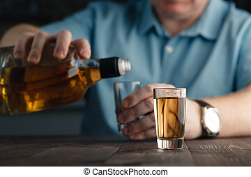 Man is pouring tequila into glass