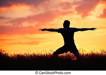 Man is practicing yoga during sunset