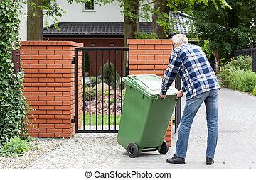 Man is pushing wheeled dumpster - Senior man is pushing ...