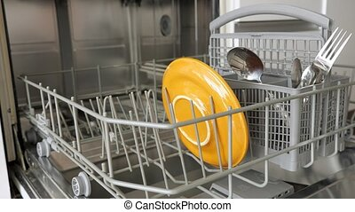Man is putting dirty tableware in dishwasher, hands closeup....