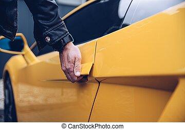 Man is reaching for the car door handle