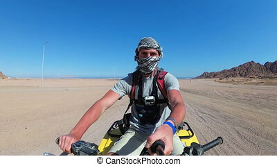 Man is Riding a Quad Bike in Desert of Egypt and Shooting...