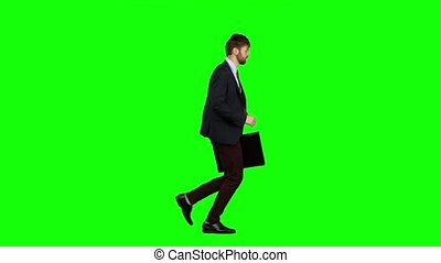 Man is running a briefcase in his hand, he rushes over it. Green screen