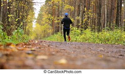 Man is running in autumn park
