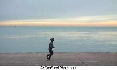 Man is running on thr ebankment. Athlete training outdoors....