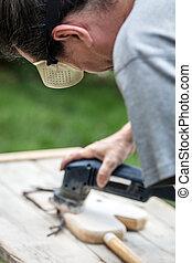 man is sanding an old hobbyhorse