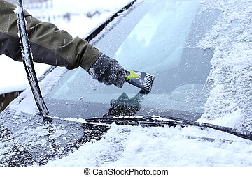 man is scraping a wind screen