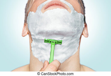 Man is shaving with green razor