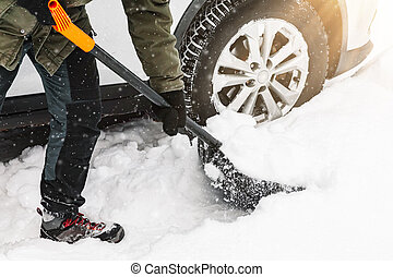 Man is shovelling snow near the car. Winter shoveling. Removing snow after blizzard