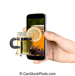 Man is showing cup with tea through mobile phone