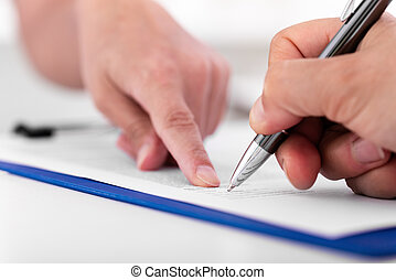 man is signing a document on a blue clipboard