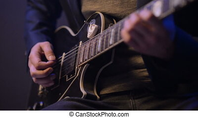 man is sitting and playing the guitar in a dark room