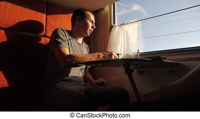 man is sitting in a Railway carriage train at the window of...
