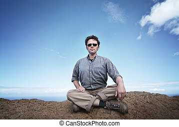 Man is sitting on a rock on top of the world, contemplating