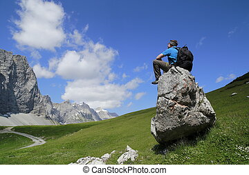 man is sitting on a stone