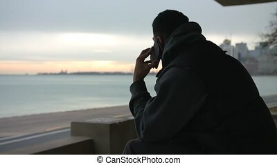 Man is sitting on the bench talking on the phone and looking at the sea