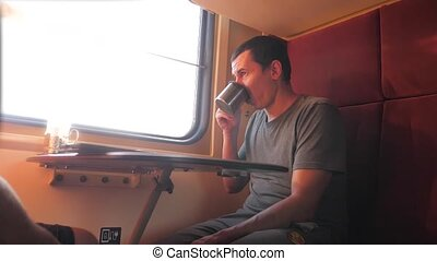 man is sitting on the train carriage holding a Railway and...